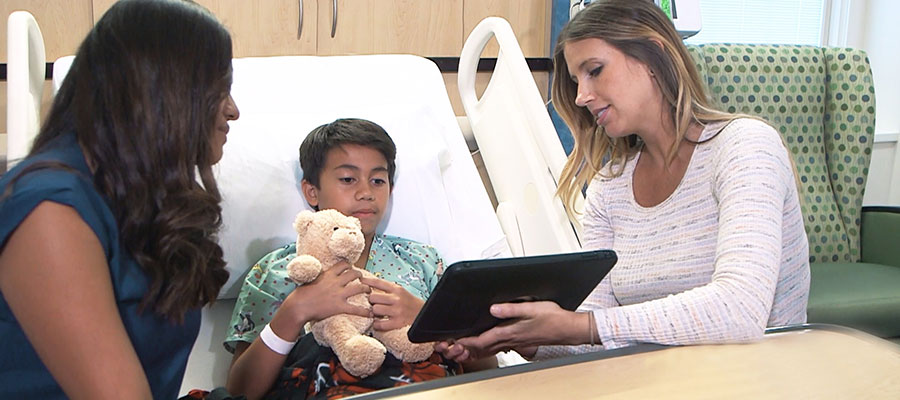 Child life specialist talking to surgery patient