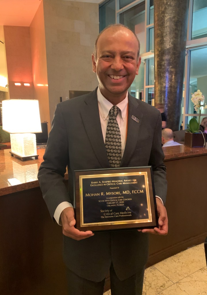 Mohan Mysore, M.D. holds Excellence in Critical Care Management award plaque