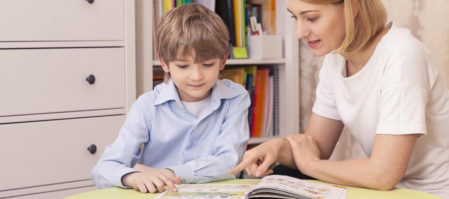 Preschool teacher and student reading a book
