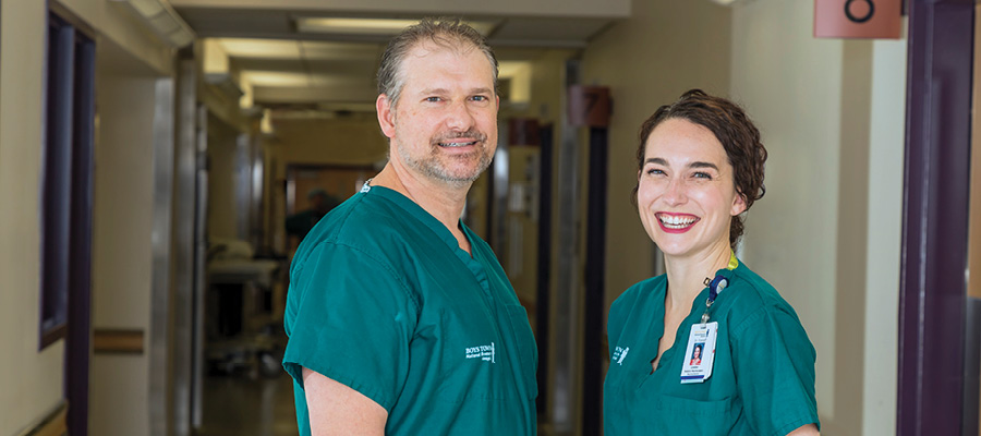 Neurosurgeons, Dr. Linden Fornoff and Dr. Mark Puccioni stand in scrubs looking at the camera and smiling