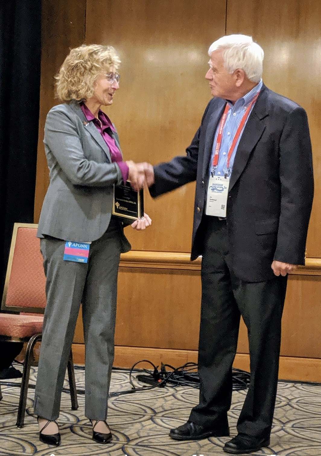 Rose Pauley, APRN and Jon Vanderhoof, M.D. shake hands as she accepts her award
