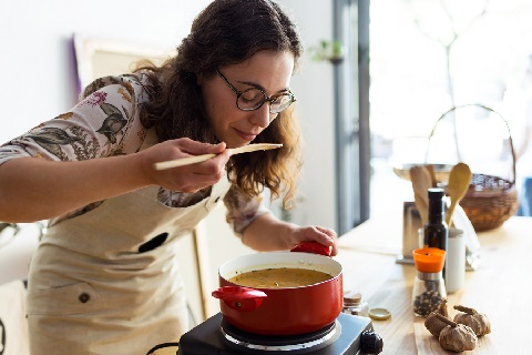 woman cooking and smelling
