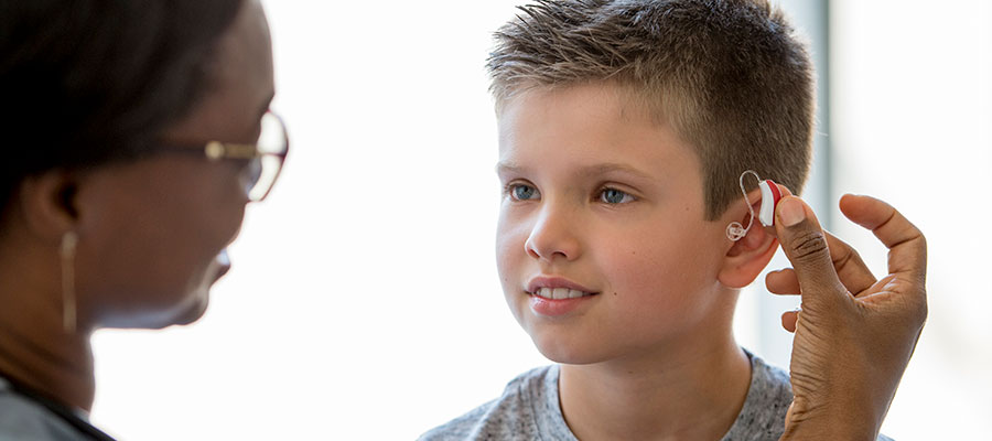 Boy fitted for small red hearing aid