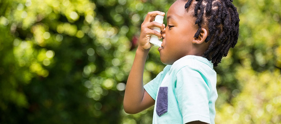 Boy breathing from asthma inhaler