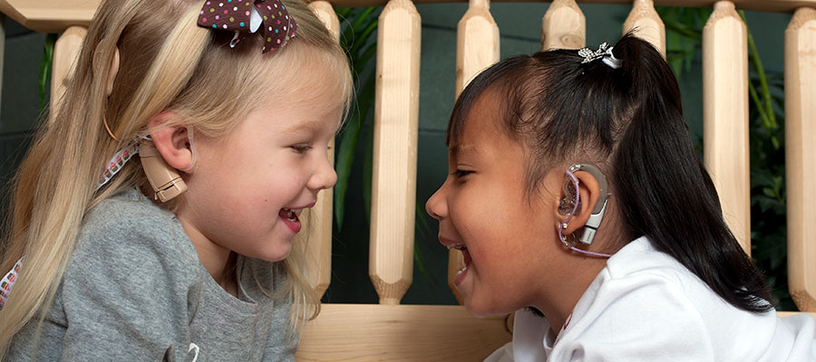 Smiling girls with cochlear implants