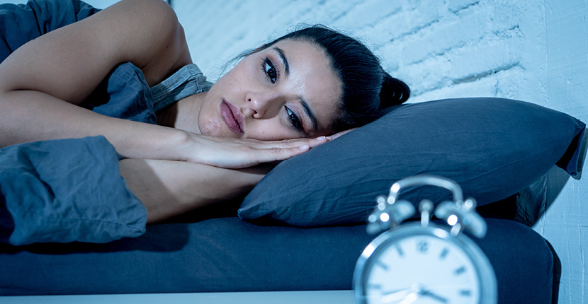 woman in bed looking at clock