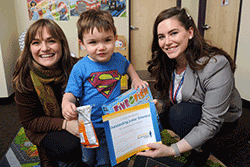 Child and mother smile for photo after participating in research. The child holds a certificate of completion and a prize.
