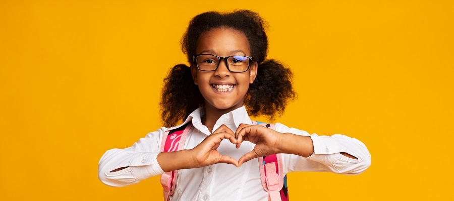 smiling girl holding her hands in a heart shape in front of her chest